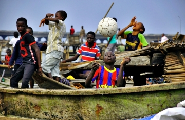 Young boys playing football on the waterfront during the demolition - one - with  UNICEF sponsored jersey.